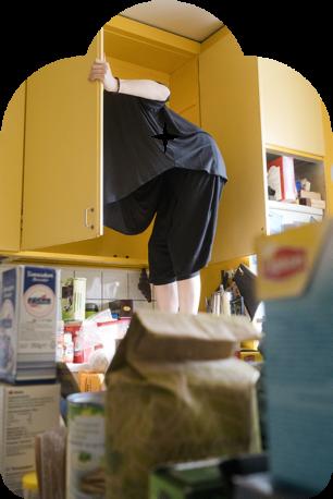 Kuvassa henkilö istuu keittiön kaapissa niin, että näkyvissä on vain jalat. Etualalla on pikaruokapussi ja teepaketti.